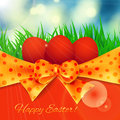 Easter card red eggs on spring background blue sky with sun rays and fresh green grass golden bow on red dots and red Royalty Free Stock Photo