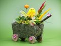 Easter cart wicker with chickling and eggs over light green background Stock Images