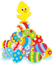 Easter chick little yellow on top of a pile of painted eggs Royalty Free Stock Photography