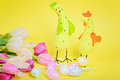 Easter chickens pink tulips and eggs over yellow paper Royalty Free Stock Image