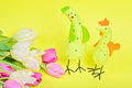 Easter chickens and pink tulips over yellow paper Stock Photography