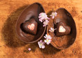 Easter chocolate egg with a surprise of two hearts decorated sprinkled with cocoa powder and almond blossom photo an open arranged Royalty Free Stock Photography