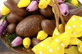 Easter chocolate hamper of eggs and bunny rabbits happy in large basket with yellow pink purple silk tulip flowers on dark Royalty Free Stock Photo