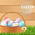 Easter colorful eggs in basket with field of grass on wooden background