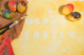 Easter colorful eggs with two painter brushes and a hand painted cloth,arranged on watercolor paper with yellow painted text. Royalty Free Stock Photo