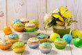 Easter colorful muffins and eggs on white table. Royalty Free Stock Photo