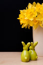 Easter composition with bunnies and narcissus still life figurines yellow flowers of in vase copyspace on black background Royalty Free Stock Photos