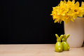 Easter composition with bunnies and narcissus still life figurines yellow flowers of in vase copyspace on black background Stock Images