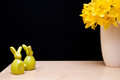 Easter composition with bunnies and narcissus still life figurines yellow flowers of in vase copyspace on black background Royalty Free Stock Images