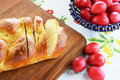 Easter concept bread and red eggs on floral tablecloth Royalty Free Stock Photo