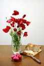 Easter concept vase of poppies red eggs and bread on table Royalty Free Stock Photography