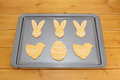 Easter cookies decorated with white frosting on a baking tray on a wooden table Stock Photography