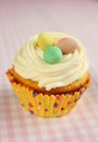 Easter cupcake vanilla with a nest and three eggs on top on a pink checkered tableclothe Stock Photography