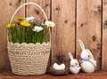 Easter decoration - basket with flowers , eggs and easter bunnies on the wooden background.