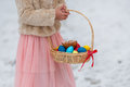 Easter decoration with colored eggs in a basket in the hands of a girl close up