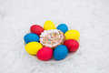 Easter decoration from colored eggs and Easter cake on a white plate