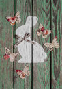 Easter decoration - painted bunny  and paper butterflies on wooden rustic background. Vintage style. Royalty Free Stock Photo