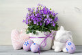 Easter design with easter eggs and a pot of flowers on a white wooden background Royalty Free Stock Photo