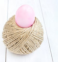 Easter egg and ball of hemp rope on wooden background rolling Royalty Free Stock Photo