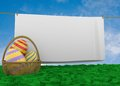 Easter egg basket with clothline eggs in lying in lush grass white sheet hanging on a clothesline space for your text Royalty Free Stock Image