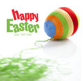 Easter egg covered with various colors wool bunch of green on first plan space for text Stock Photo