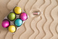 Easter egg hunt at the beach with an overhead view of a carton of colorful dyed or painted eggs on golden sand with a ridged wavy Stock Image