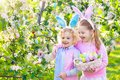 Easter egg hunt. Kids with bunny ears and basket. Royalty Free Stock Photo