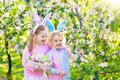Easter egg hunt. Kids with bunny ears and basket.