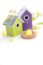 Easter egg in a nest with birdhouses and birch branches on backgr yellow green violet birdnests fresh background Stock Photo