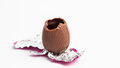 Easter egg unwrapped pink foil bite taken out white background Royalty Free Stock Photos
