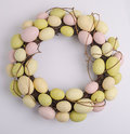 Easter egg wreath an made up of dried up branches and eggs painted in pale pastel colors pink green and yellow isolated on while Royalty Free Stock Photography