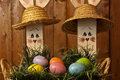 Easter eggs assorted colored in wicker basket on green grass with wooden rabbits in background Stock Photography