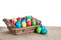 Easter eggs in the basket painted colorful on sackcloth on white background Stock Image