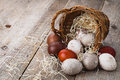 Easter eggs in basket on wooden background Stock Photo