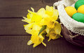 Easter eggs in the basket on wooden table with bouquet of daffodil