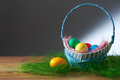 Easter eggs in a basket on a wooden table.