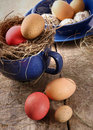 Easter eggs in blue enamel cup with straw Royalty Free Stock Images