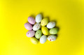 Easter eggs candy at yellow multi coloured confection background Stock Images