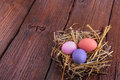 Easter eggs colorful in the nest on the wooden table Stock Photo