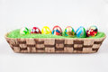 Easter eggs colorful in wicked pannier on a white background Royalty Free Stock Photo