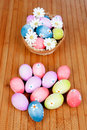 Easter eggs decorated with daisies tucked in a basket on wooden background Royalty Free Stock Photo