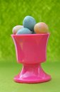 Easter eggs in eggcup small pink on green background Stock Photo
