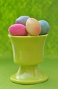 Easter eggs in eggcup small pink on green background Royalty Free Stock Photos