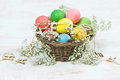 Easter eggs with flowers over bright wooden background