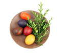Easter eggs green sprig brown plate white background Stock Photos