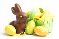 Easter eggs green wicker basket chocolate bunny Royalty Free Stock Photos