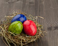 Easter eggs in hay nest on dark wood red green and blue brown wooden table Royalty Free Stock Photo