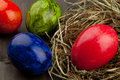Easter eggs in hay nest on dark wood red green and blue brown wooden table Royalty Free Stock Photography