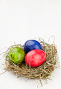 Easter eggs in hay nest on white wood red green and blue wooden table Stock Photo