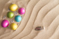 Easter eggs hidden at the beach for the egg hunt colorful decorated dyed traditional with a decorative pattern of wavy diagonal Stock Photo